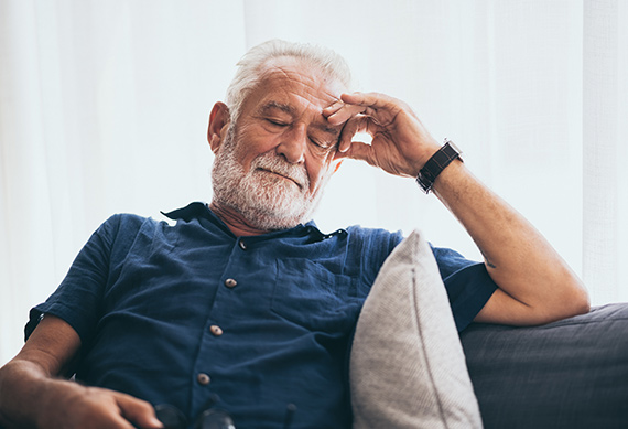 An old man resting on a couch with eyes closed