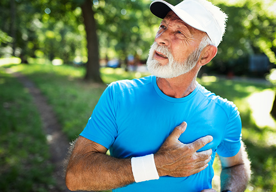 A sportful old man with hands to the chest